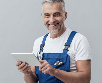 Man with tablet smiles at the viewer